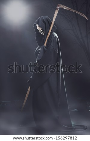 death with scythe standing in the fog at night in the cemetery - stock photo