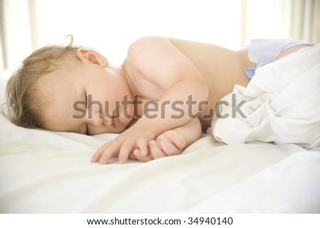 deautiful baby boy sleeping on a white blanket - stock photo