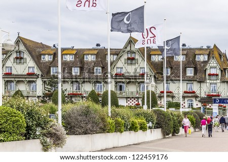 DEAUVILLE - JULY 18: A pedestrian walks past Normandy Barriere hotel on July 18, 2012, Deauville, France. 5 star hotel has 290 rooms and was constructed in 1913 and is famous for half-timbering decor. - stock photo