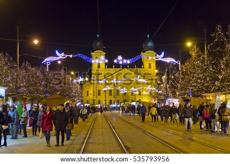 DEBRECEN, HUNGARY - DECEMBER 13, 2016: People walking during traditional Christmas holiday Market on Kossuth square (Kossuth ter) in center of Debrecen, Hungary. Protestant Great Church on background