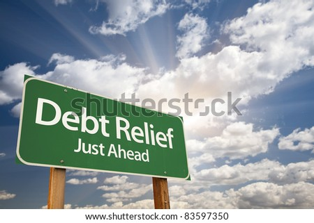 Debt Relief, Just Ahead Green Road Sign Over Dramatic Sky, Clouds and Sunburst. - stock photo