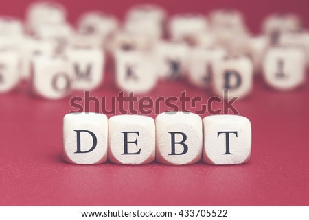 Debt word written on wood cube with red background - stock photo