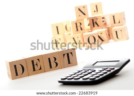 Debt word written with puzzle blocks and calculator over white