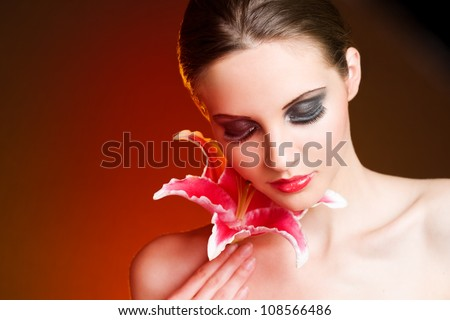 Decadent beauty, colorful portrait of gorgeous young brunette with colorful flower. - stock photo