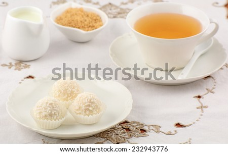 Decadent white chocolate and coconut candies with refreshing herbal tea in horizontal format - stock photo