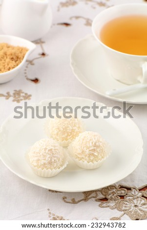 Decadent white chocolate and coconut candies with refreshing herbal tea in vertical format - stock photo