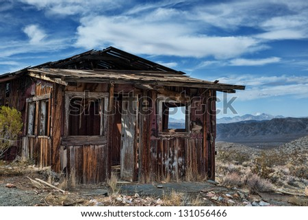 Decayed cabin on hill in Randsberg California with beautiful cloudy sky and mountains in the back ground - stock photo