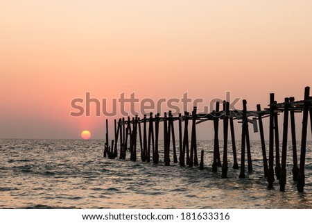 Decaying wooden bridge in the sea with sunset