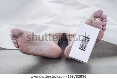 deceased man with a bar code on his toe tag, covered in a white sheet - stock photo