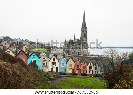December 2017, Cobh, Cork, Ireland - The cathedral and the tipical colored houses in a very cloudy day