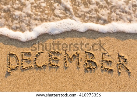 December - word drawn on the sand beach with the soft wave. Months series of 12 pictures. - stock photo