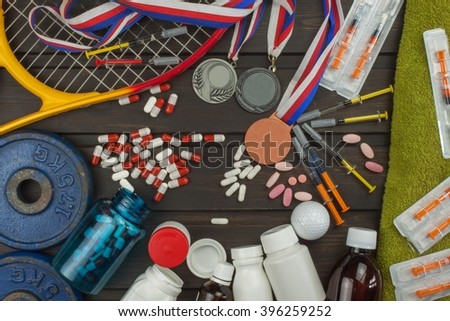 Deception in sports. Doping for athletes. Scammers in the sport. Abuse of anabolic steroids for sports. Anabolic steroids spilled on a wooden table. Fraud in sports. - stock photo