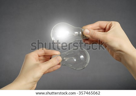 Decision making concept. Hands holding two light bulbs, one of them is glowing. - stock photo