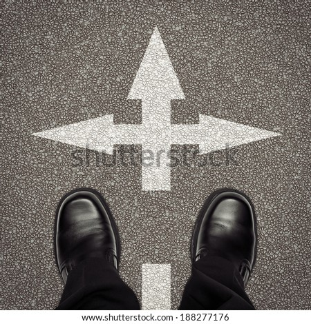 Decision or direction concept with arrows and shoes on road - stock photo