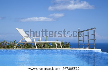 Deck chair at an turquoise infinity pool - stock photo