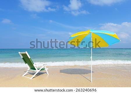 Deck chair with beach umbrella - stock photo