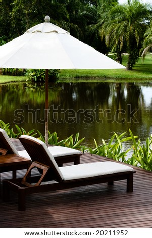 Deck chairs and umbrellas next to a lake. - stock photo