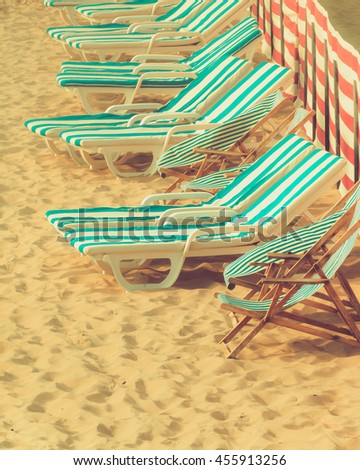 Deck chairs and wind screen with striped pattern on sunny beach - stock photo