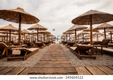 deck chairs on the beach resort town. sunbeds and umbrellas at the coast! - stock photo