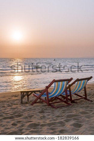 Deck chairs on the sand on sea sunset