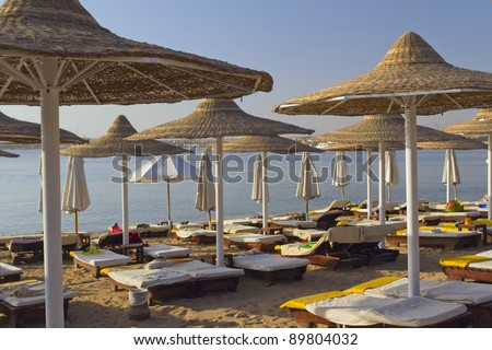 Deck chairs under an umbrella on a beach in the hot afternoon sun-horizontally. (Red Sea, Egypt) - stock photo