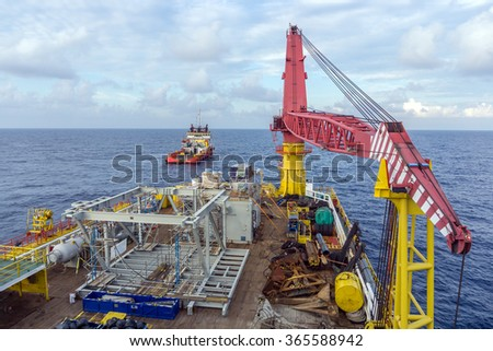 Deck view of construction barge with anchor handling tug in the background
