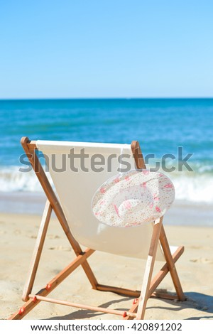 Deckchair and female hat on stunning tropical beach vacation background. Happy time - stock photo