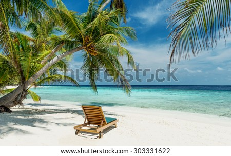 deckchair on a beautiful untouched tropical beach - stock photo