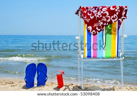 deckchair, swim suit, flip-flops and cocktail on the beach - stock photo