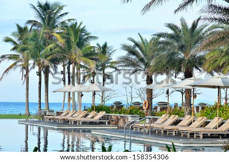 Deckchairs by tropical resort hotel pool - stock photo