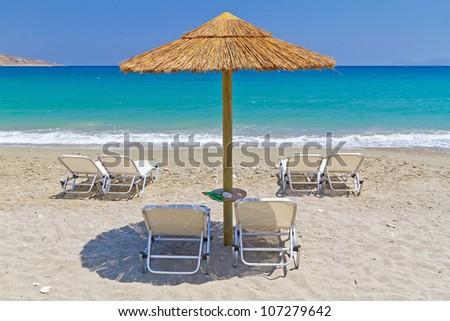 Deckchairs under parasol at Aegean Sea of Greece - stock photo
