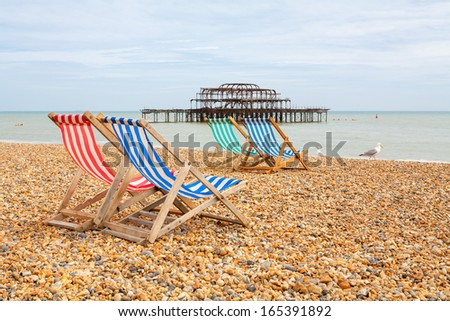 Deckhairs on Brighton beach with West Pier behind. Brighton, East Sussex, England - stock photo