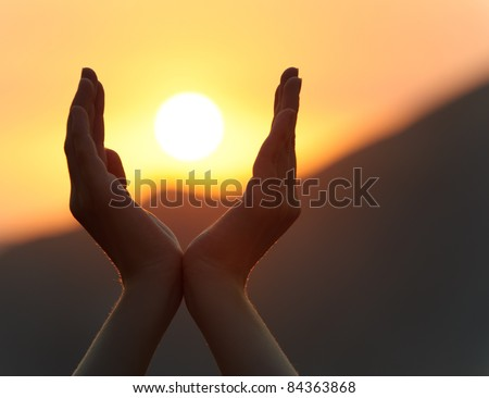 Decline in hands. A sunset on a background of the lifted female hands - stock photo