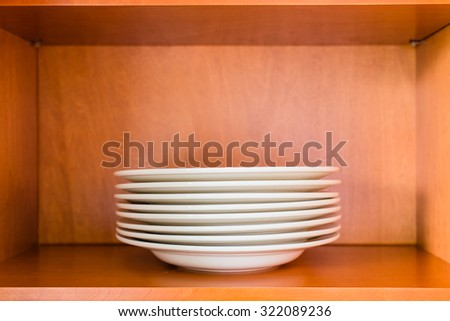 Decluttered minimalistic kitchen cabinet for simple living. Contains one single type of plates: white porcelain pasta or soup bowl plates. - stock photo