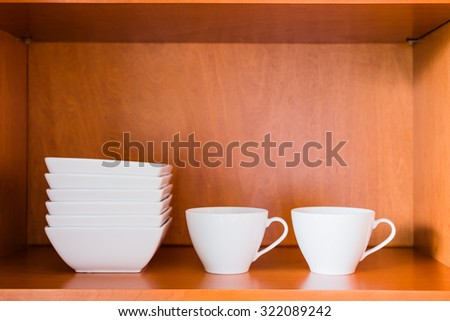 Decluttered minimalistic kitchen cabinet for simple living. Contains only essentials: white porcelain bowls and coffee or tea cups.