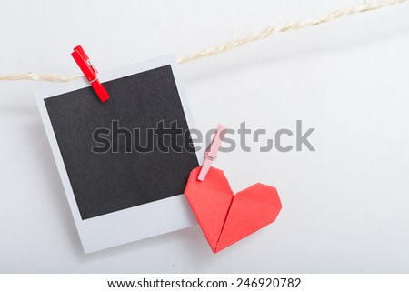 Deco for love day. Empty instant photo and origami hearts hanging on clothesline - stock photo