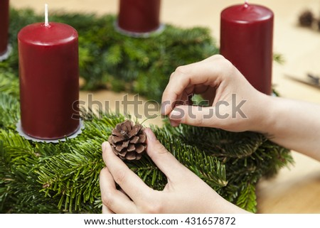 Decorate an advent wreath with pinecone - stock photo