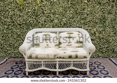 Decorate sofa and carpet against the green small tree wall. - stock photo