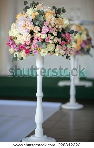 Decorate wedding bouquet of fresh beautiful flowers of roses and peony white pink violet purple yellow lilac and orange colours in slim long vase on tile floor background, vertical picture - stock photo