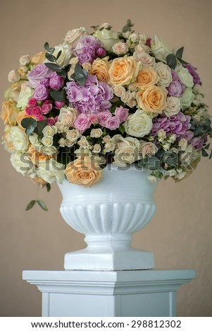Decorate wedding bunch of fresh beautiful flowers of roses and peony white pink violet purple yellow lilac and orange colours in big vase on beige background, vertical picture - stock photo