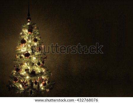 Decorated and lit Christmas tree on plain background