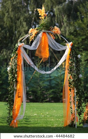 Decorated archway for wedding ceremony with colorful flowers and ribbons - stock photo