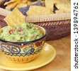 Decorated bowl of guacamole dip with a basket of tortilla chips. - stock photo
