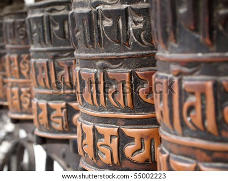 Decorated buddhist prayer wheels in a stupa. - stock photo