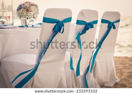 Decorated chairs at dining table on the beach for special guests at a wedding ceremony. - stock photo