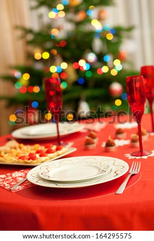 Decorated christmas dining table with champagne glasses and christmas tree in background