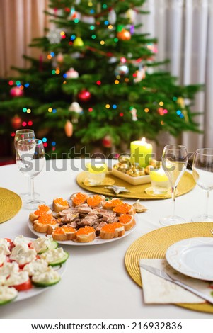 Decorated Christmas dining table with Christmas tree in background - stock photo