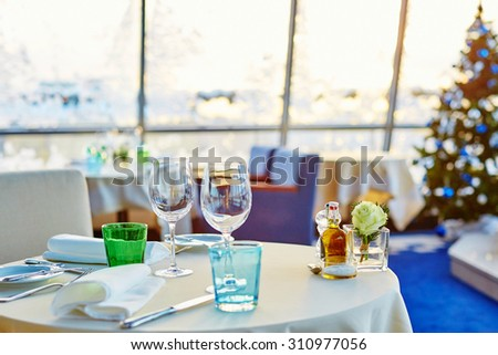 Decorated christmas dining table with wine glasses and christmas tree in background - stock photo