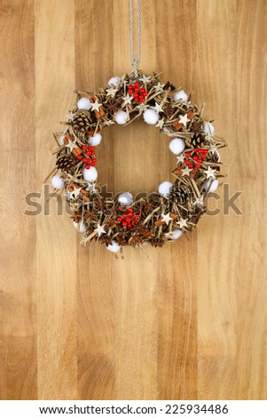 Decorated christmas door wreath with birch stars, cinnamon sticks, anise stars and pine cones brown twigs on sapele wood background, copy space - stock photo