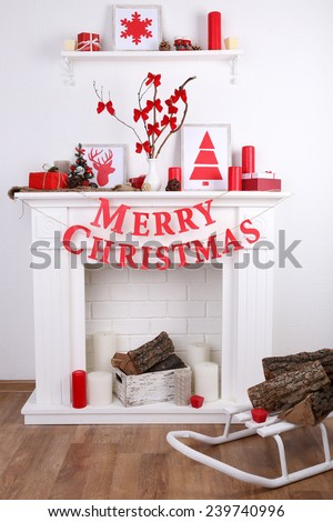 "Decorated Christmas fireplace with inscription ""Merry Christmas"" on white wall background - stock photo"
